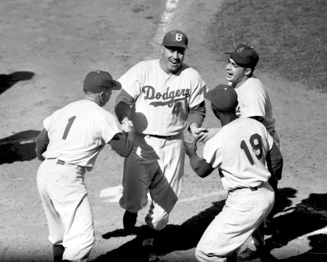 BROOKLYN, NY - OCTOBER 5: Duke Snider #4 of the Brooklyn Dodgers is greeted at home plate by teammembers Jim Gilliam #19, Pee Wee Reese #1 and the batboy after homering in World Series Game 2 against the New York Yankees at Ebbets Field on October 5, 1955 in Brooklyn, New York. (Photo by Kidwiler Collection/Diamond Images/Getty Images)